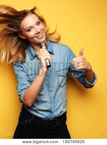 Portrait of a charming blonde woman singing with microphone in studio over yellow background.