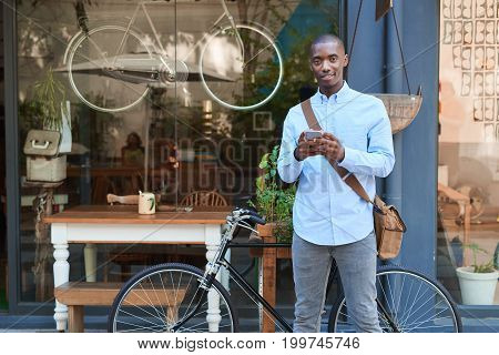 Portrait of a stylish young African man smiling and reading a text message on his cellphone while standing with his bicycle on a city street