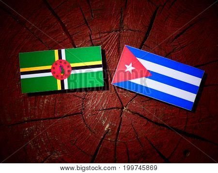 Dominica Flag With Cuban Flag On A Tree Stump Isolated