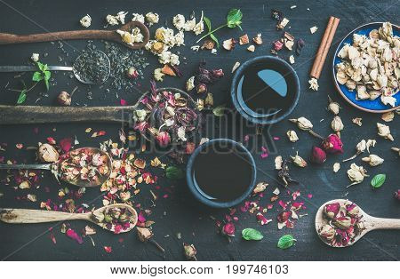 Chinese black tea in black stoneware cups and wooden spoons with dry herbs, flower buds and leaves over black wooden background, top view, horizontal composition