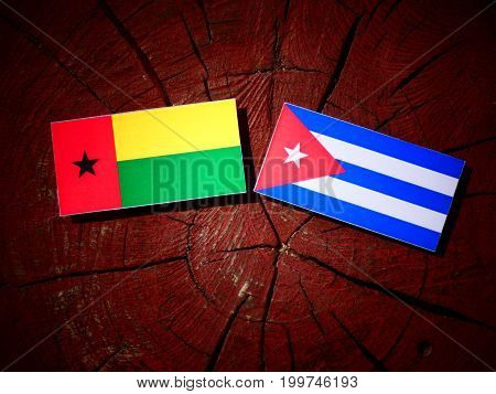 Guinea Bissau Flag With Cuban Flag On A Tree Stump Isolated