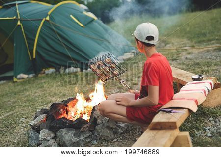 Family with a tent on a picnic with a fire. The boy sits by the fire and fry the bread on the barbecue grill. focus on the fireplace