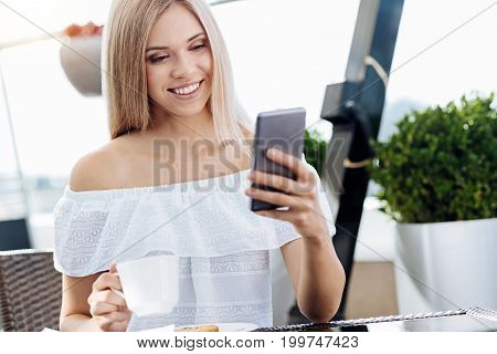 Pleasant message. Delighted happy young woman holding her cell phone and smiling while receiving a pleasant message