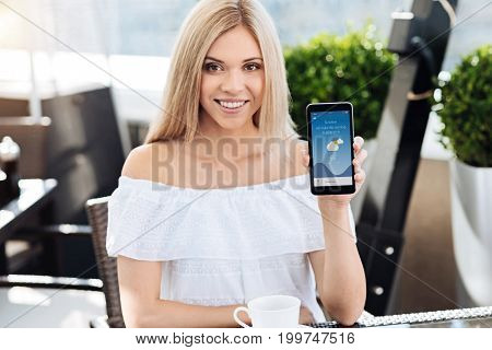 Modern technology. Delighted positive blonde woman sitting at the table and holding her smartphone while showing it to you