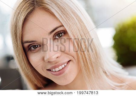 Beautiful face. Delighted nice young woman looking at you and smiling while being in a great mood