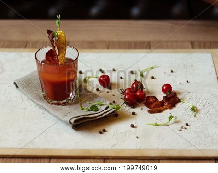 A top view of cherry tomatoes, fragrant peppercorns, and herbs on a light fabric on a wooden table. A glass of Bloody Mary with bacon and slice of potato on a top of a glass on a blurred background.