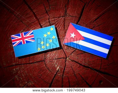 Tuvalu Flag With Cuban Flag On A Tree Stump Isolated