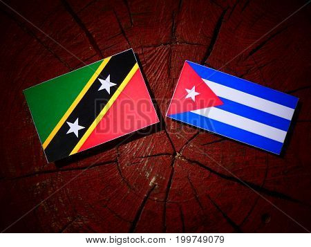 Saint Kitts And Nevis Flag With Cuban Flag On A Tree Stump Isolated
