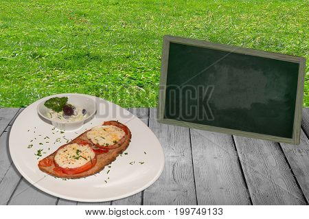 Slice of Bread with tomato baked with cheese on a wooden table. In the background meadow and a blackboard.