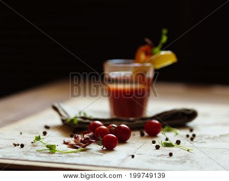 A pile of natural cherry tomatoes, spicy peppercorns and green herbs on a light fabric and on a black blurred background. A glass of Bloody Mary with piece of bacon and potato on a top of a glass.