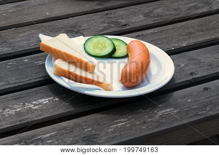 Bock sausage wieners or Frankfurther sausage with toast and cucumbers on a white plate.