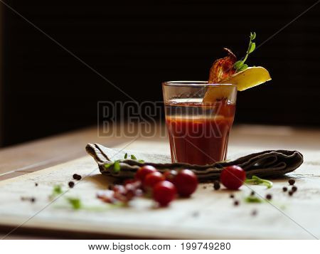 A glass of Bloody Mary with piece of bacon and potato on a top of a glass on a black blurred background. A pile of natural cherry tomatoes, spicy peppercorns and green herbs on a white tablecloth.