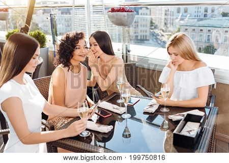 Female talks. Nice cheerful young woman leaning forward and whispering gossips in her friends ear while discussing people they know