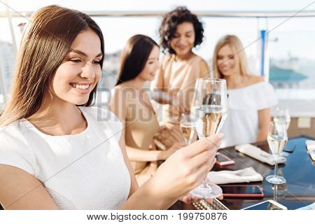 Drinking champagne. Joyful positive pretty woman looking at her glass with champagne and smiling while having a good time