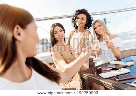 To you. Delighted nice young women looking at their friend and drinking to her while having a bachelorette party in her honor