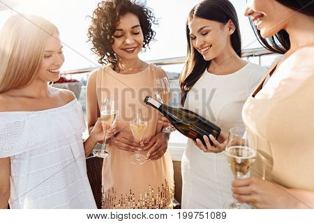 Time for celebration. Good looking happy pretty women holding glasses and enjoying their champagne while having a hen party