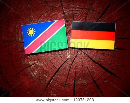 Namibian Flag With German Flag On A Tree Stump Isolated
