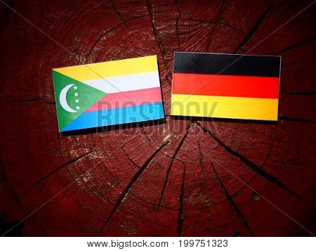 Comoros Flag With German Flag On A Tree Stump Isolated