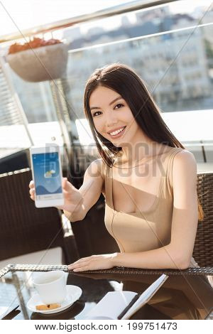 My lockscreen. Happy positive Asian woman sitting at the table and holding her smartphone while showing you her lockscreen