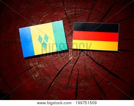 Saint Vincent And The Grenadines Flag With German Flag On A Tree Stump Isolated