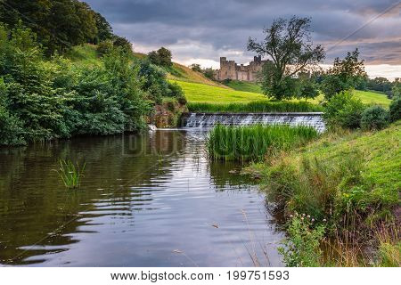 River Aln Weir below Alnwick Town and Castle. The River Aln runs through Northumberland from Alnham to Alnmouth. Here below Alnwick Town and Castle is one of the weirs along its length