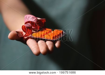 Young woman with pack of pills and measuring tape, closeup. Weight loss concept
