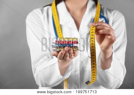 Doctor holding packs of pills and measuring tape in hands. Weight loss concept