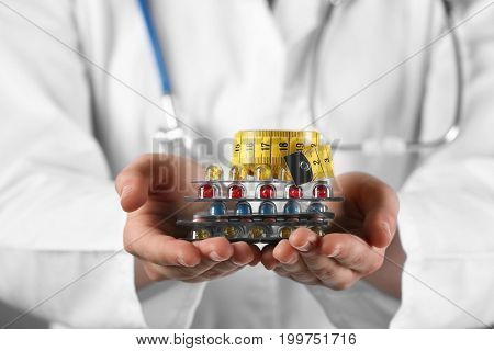 Doctor holding packs of pills and measuring tape in hands, closeup. Weight loss concept