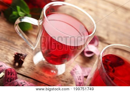 Cups of hibiscus tea and measuring tape on wooden table. Weight loss concept