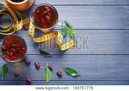 Composition with brier tea and measuring tape on wooden table. Weight loss concept