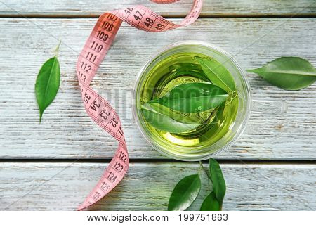 Cup of tea with leaves and measuring tape on wooden table. Weight loss concept
