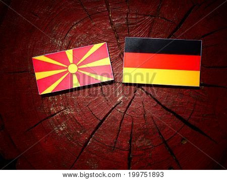 Macedonian Flag With German Flag On A Tree Stump Isolated