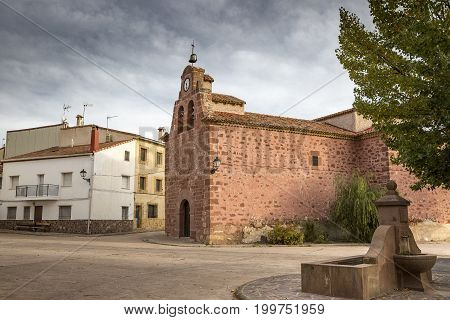 a street and San Juan Bautista parish church in Chequilla village, Province of Guadalajara, Spain