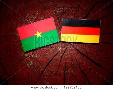 Burkina Faso Flag With German Flag On A Tree Stump Isolated
