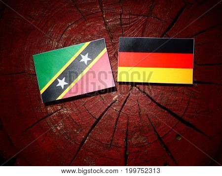 Saint Kitts And Nevis Flag With German Flag On A Tree Stump Isolated