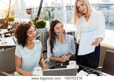 My ideas. Delighted positive blonde woman holding a document and presenting her ideas to colleagues while working with them