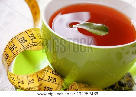 Closeup view of cup with tea, leaf and measuring tape on table. Weight loss concept