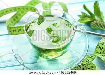 Cup of mint tea and measuring tape on wooden table. Weight loss concept