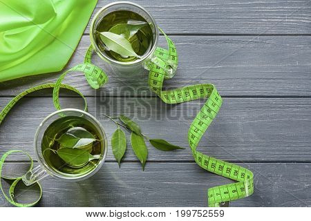 Cups of tea and measuring tape on wooden table. Weight loss concept
