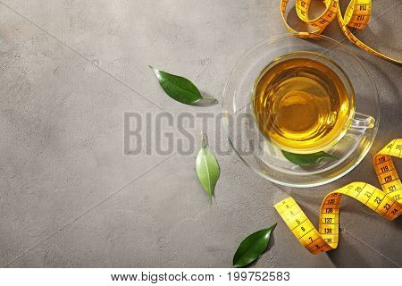 Cup of tea and measuring tape on table. Weight loss concept
