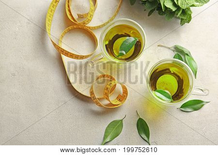 Cups of tea and measuring tape on table. Weight loss concept