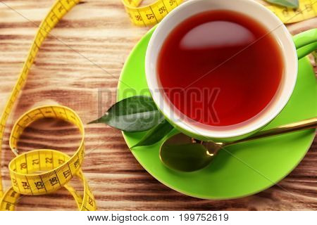 Cup of tea and measuring tape on wooden table. Weight loss concept