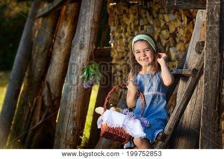 child smiling with no teeth sitting near the wooden wall of the shed