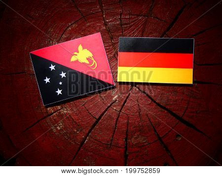 Papua New Guinea Flag With German Flag On A Tree Stump Isolated