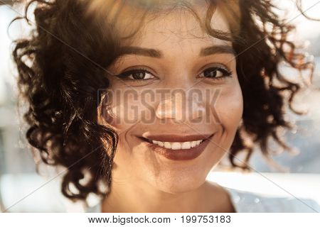 Young and beautiful. Positive cheerful happy woman smiling and looking at you while showing her emotions