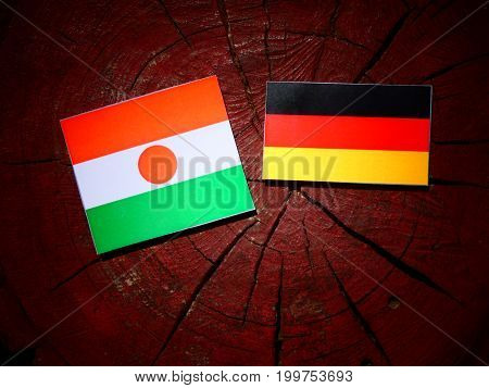 Niger Flag With German Flag On A Tree Stump Isolated