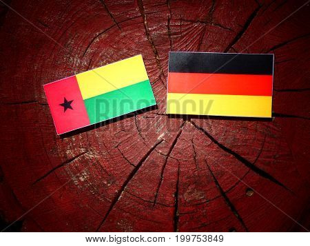 Guinea Bissau Flag With German Flag On A Tree Stump Isolated