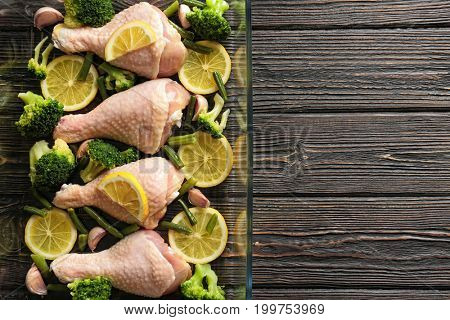 Fresh chicken legs with lemon and broccoli in baking dish on wooden table