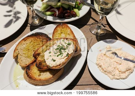 Hot pepper cheese dip and slices of grilled bread an an appetizer in greek tavern. Horizontal. Daylight. View from above.