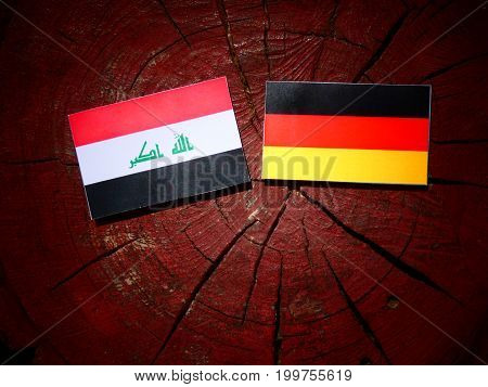 Iraqi Flag With German Flag On A Tree Stump Isolated